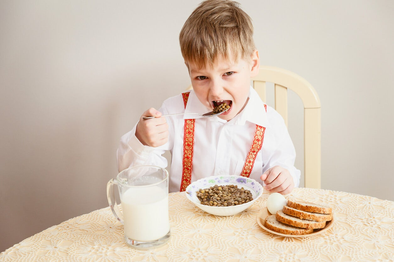Niño comiendo lentejas porque las legumbres son muy importantes.