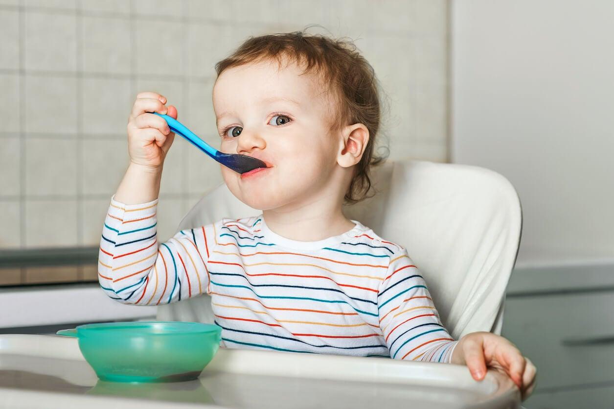 Niño comiendo puré de verduras como parte de un menú para bebés de 18 meses.