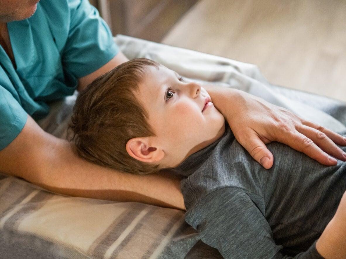Niño en fisioterapia infantil con dolor de cuello.