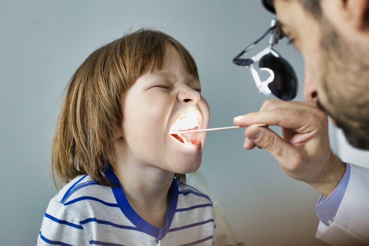Niño en el médico con dolor de garganta.