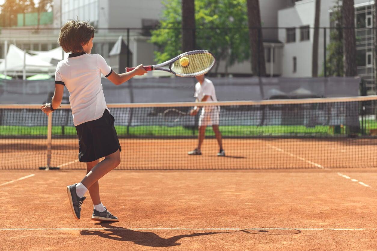 Niño jugando al tenis.