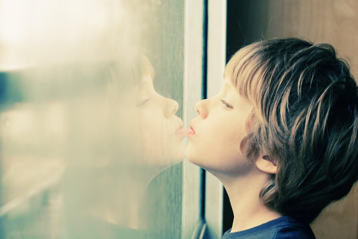 Niño con autismo mirando por la ventana.