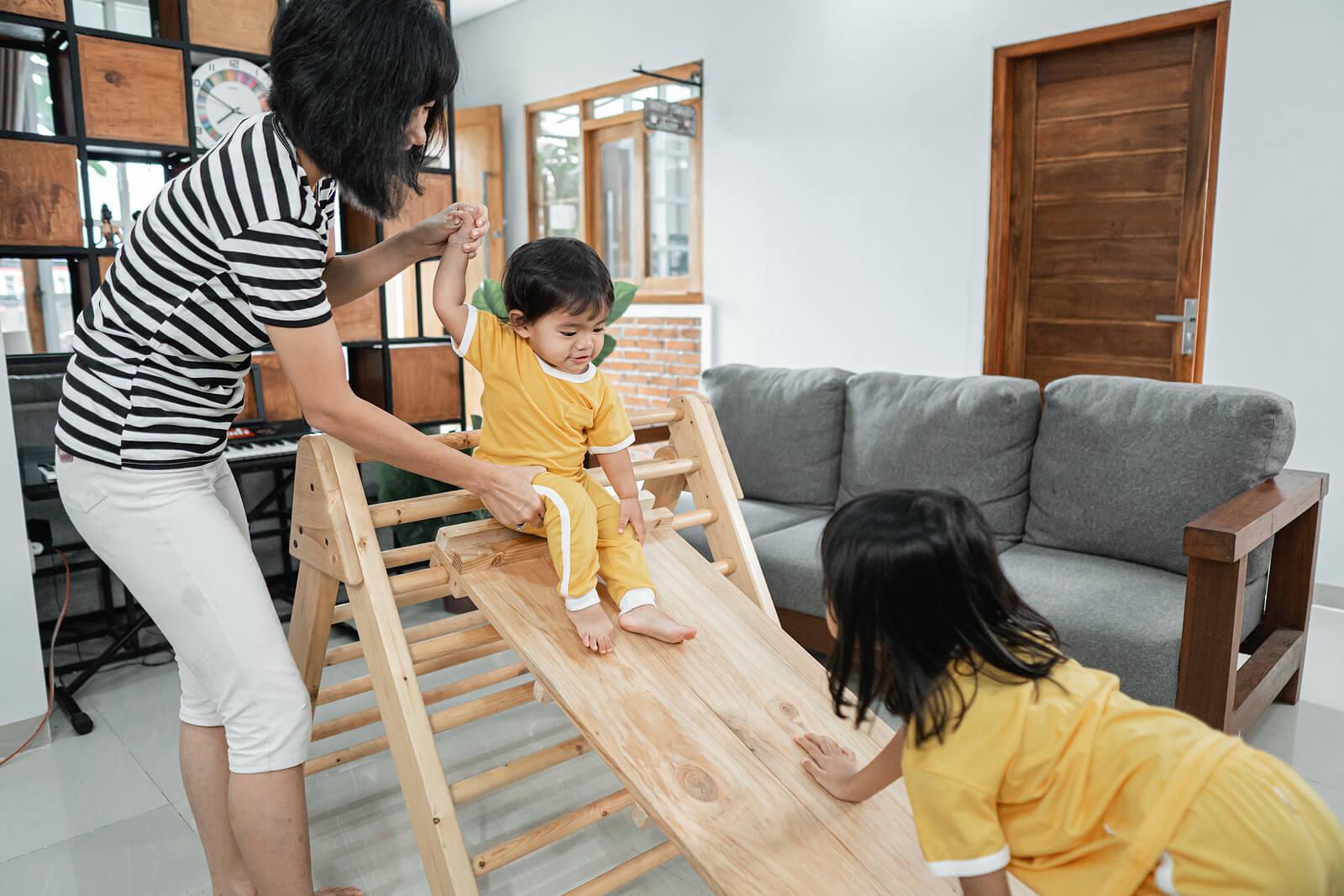 Madre con sus hijos aplicando el método Pikler para promover el movimiento libre en bebés.