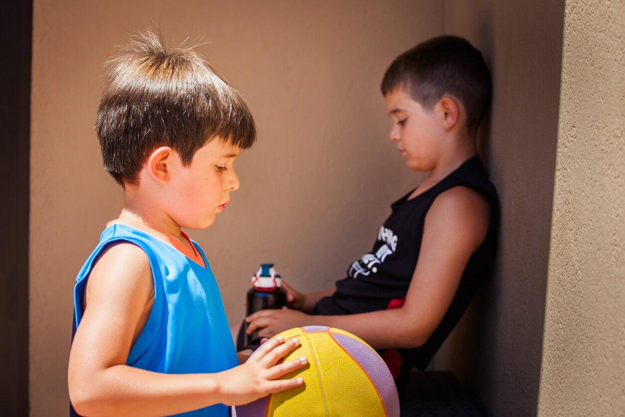 Deux enfants démotivés avec un ballon.