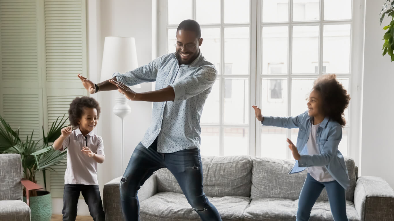 Padre bailando con sus hijos.