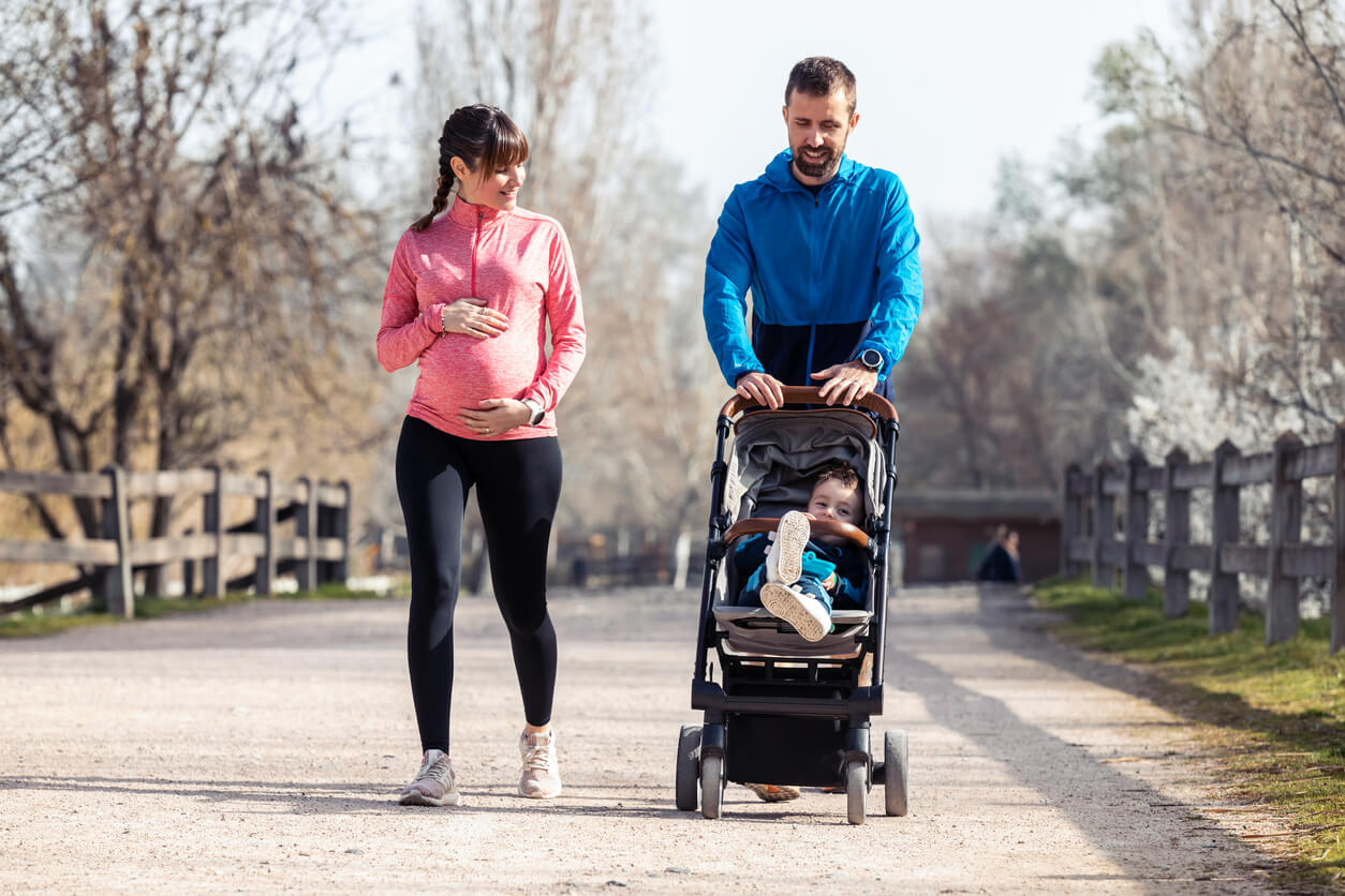 Pareja practicando deporte con su hijo en el carrito.