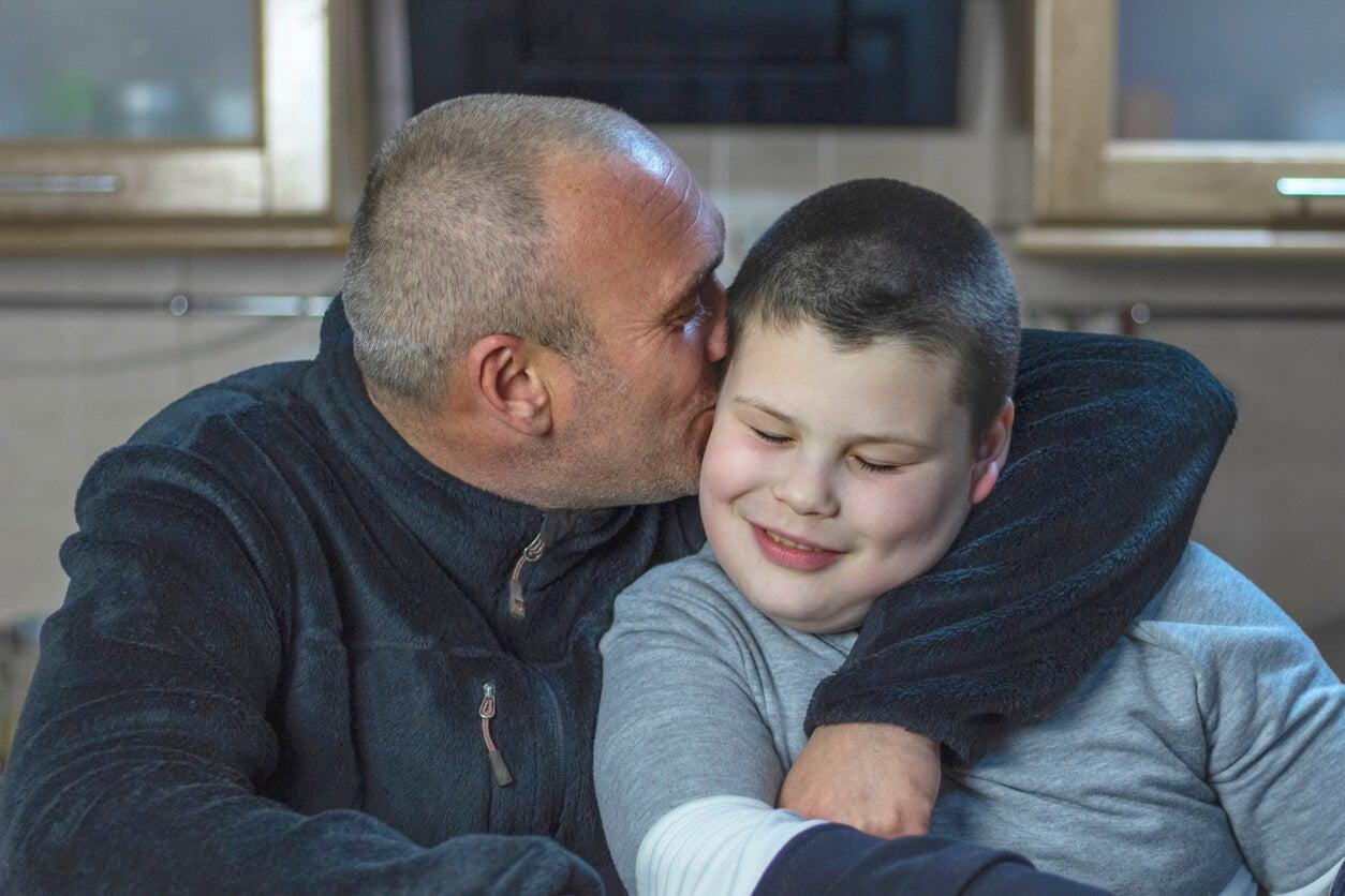 Padre dando un beso a su hijo después de hacer la prueba para identificar el autismo en los niños.