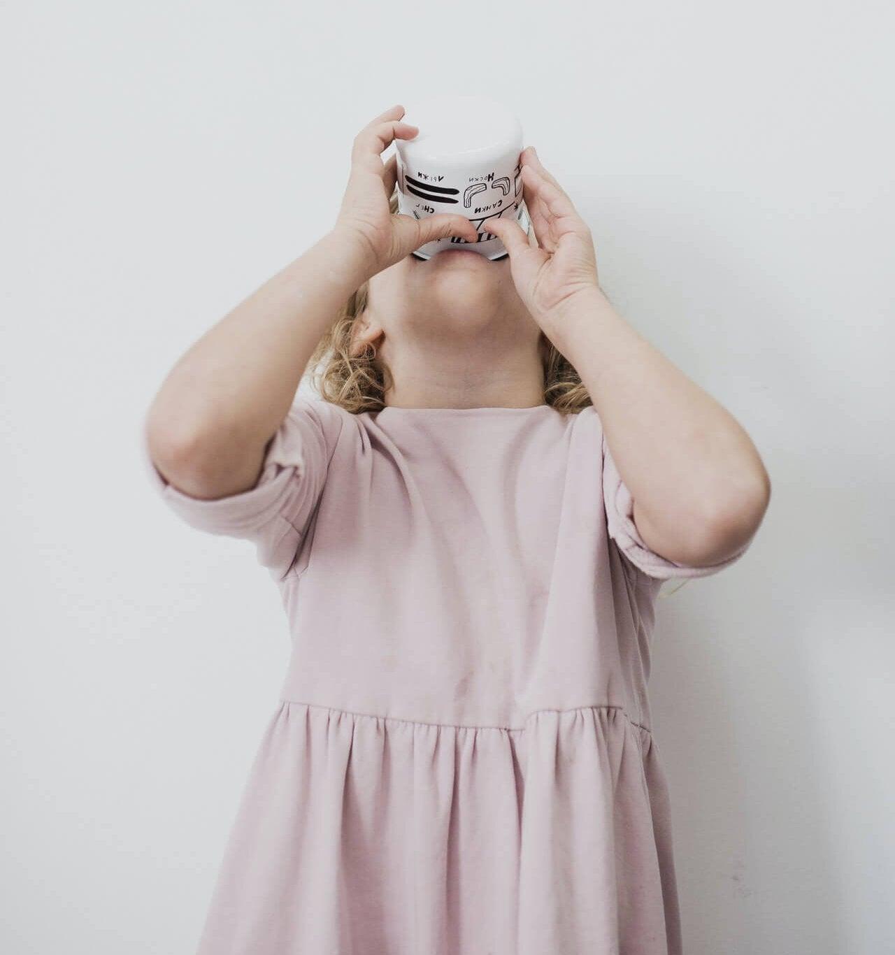 Une jeune fille qui boit un yaourt liquide.