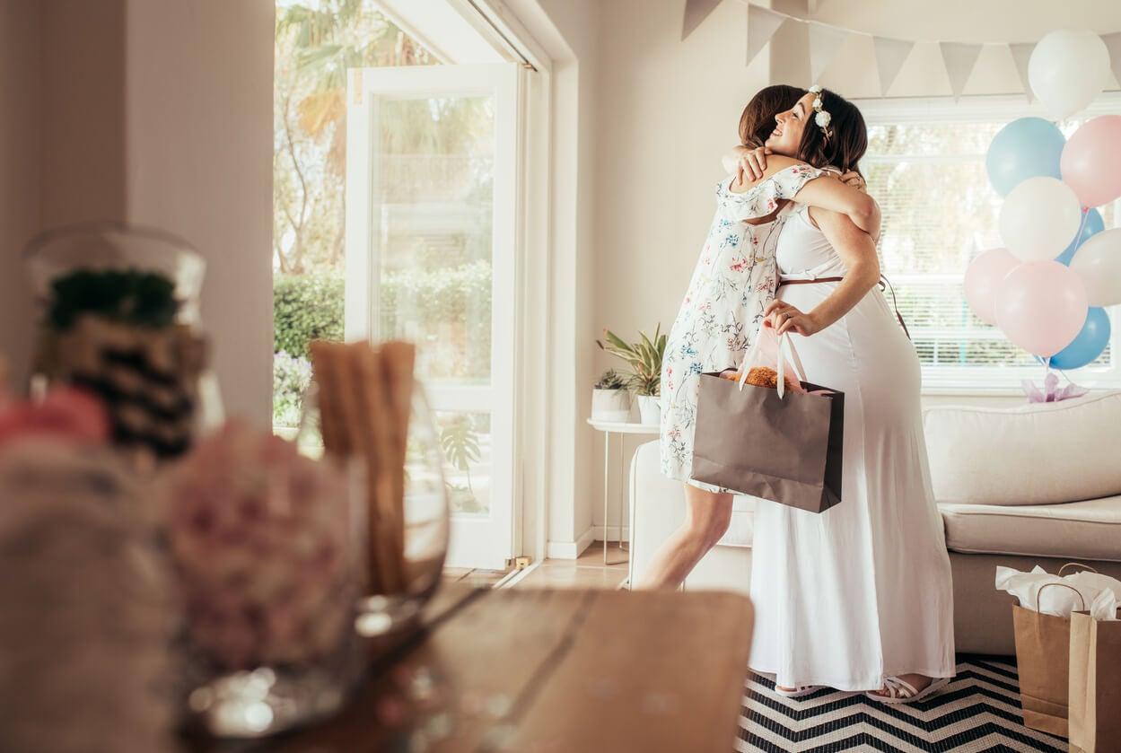 Amiga dando un abrazo a la futura mamá en el baby shower..