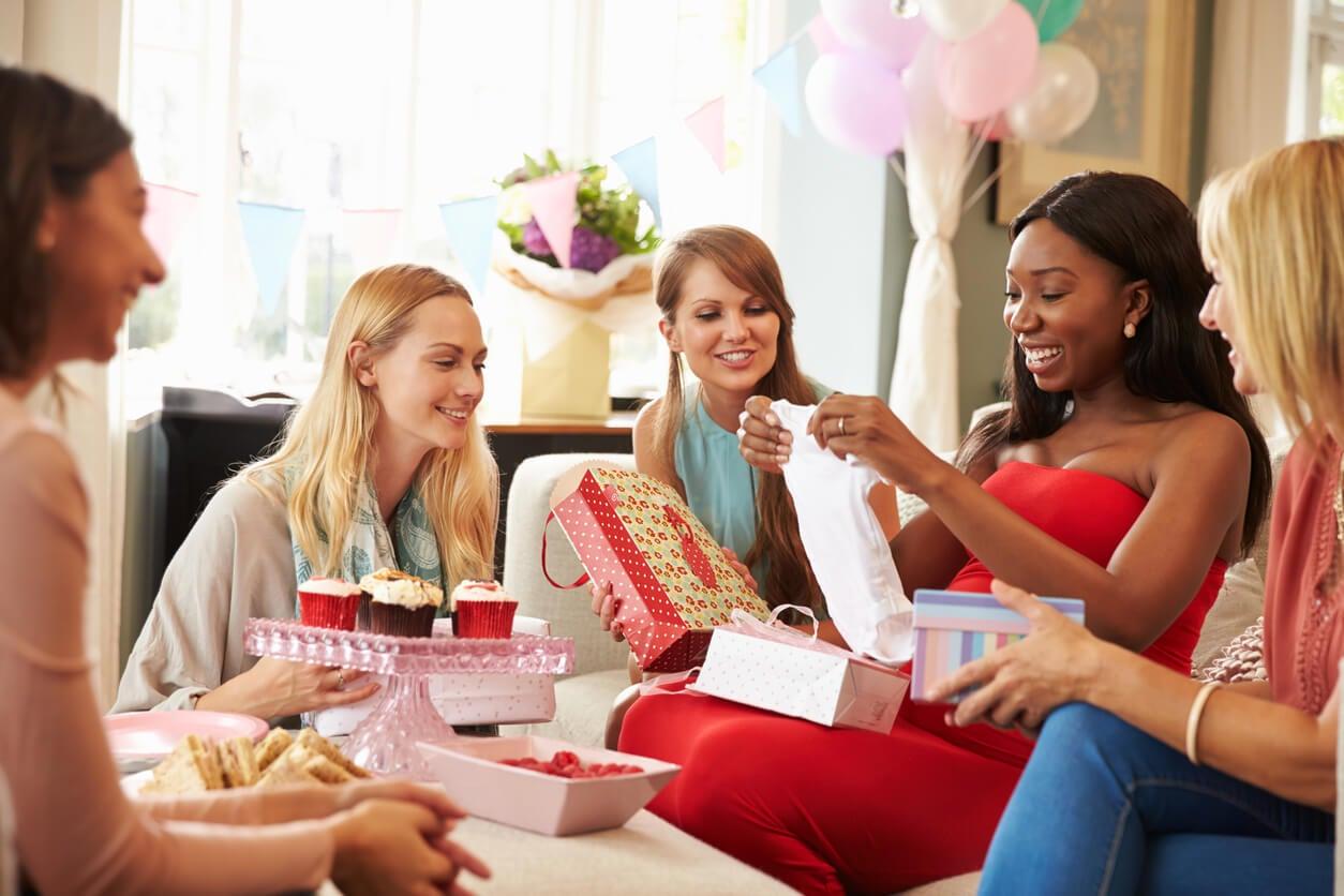 Amigas en un baby shower entregando los regalos.