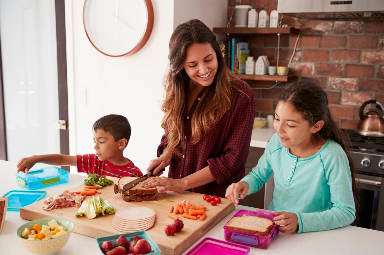 Madre con sus hijos en la cocina preparando platos saludables con todos los nutrientes necesarios.