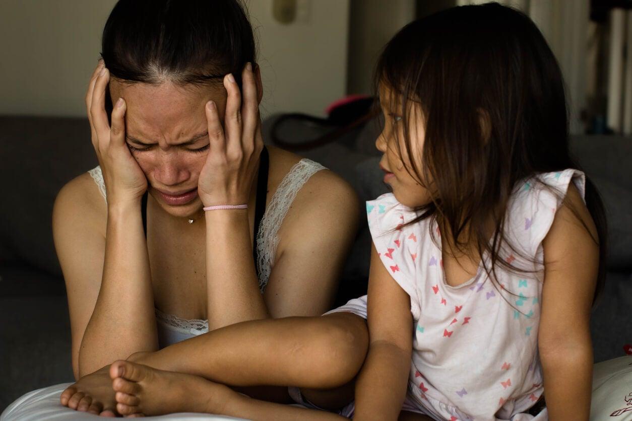 Madre llorando frente a su hija porque padece depresión.