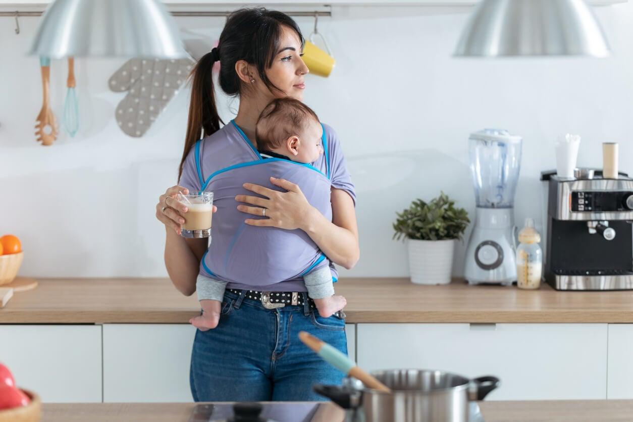 Madre tomando café con un bebé en brazos para bajar de peso después del parto.