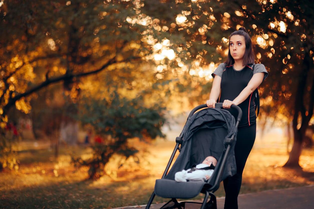 Une femme qui marche avec son bébé dans la poussette.