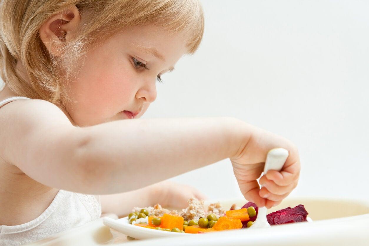 Niña comiendo de manera saludable para prevenir trastornos alimentarios.