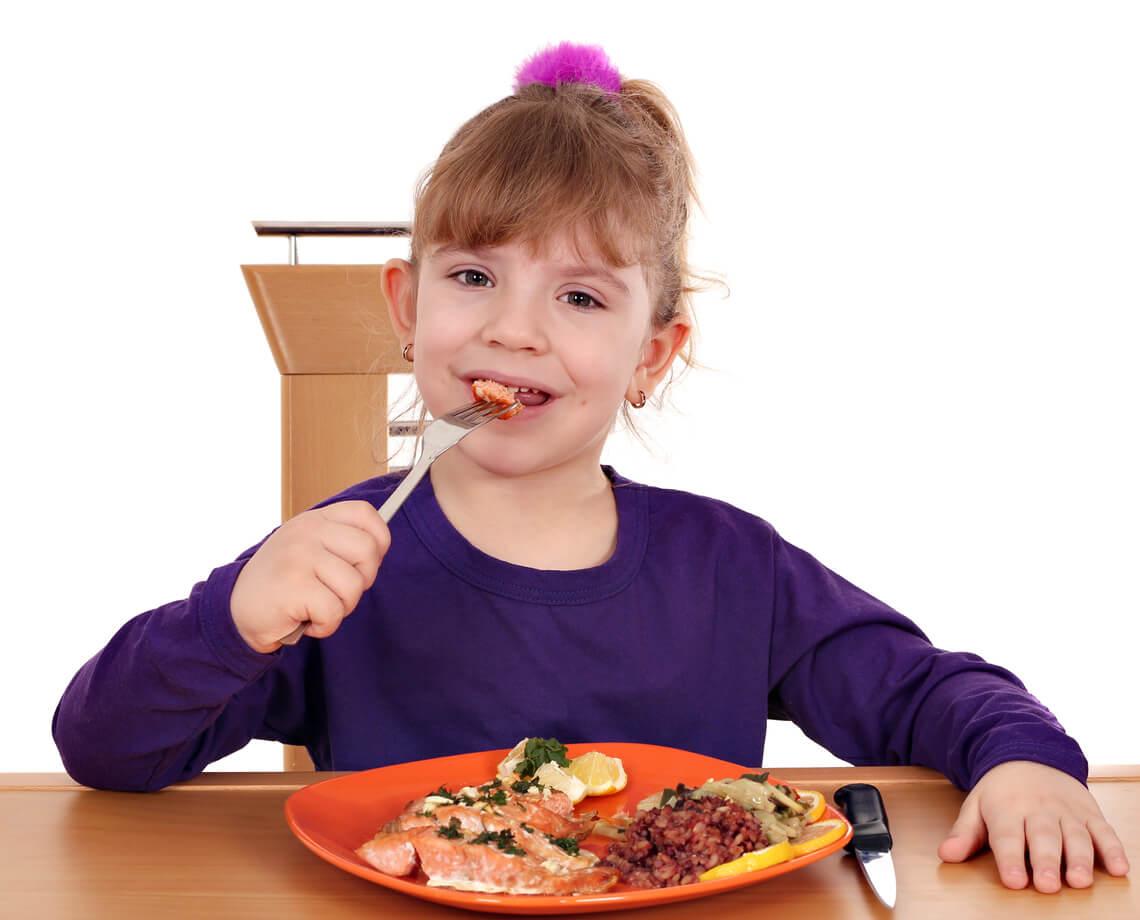 Niña comiendo salmón, uno de los alimentos que cuidan el corazón del niño.