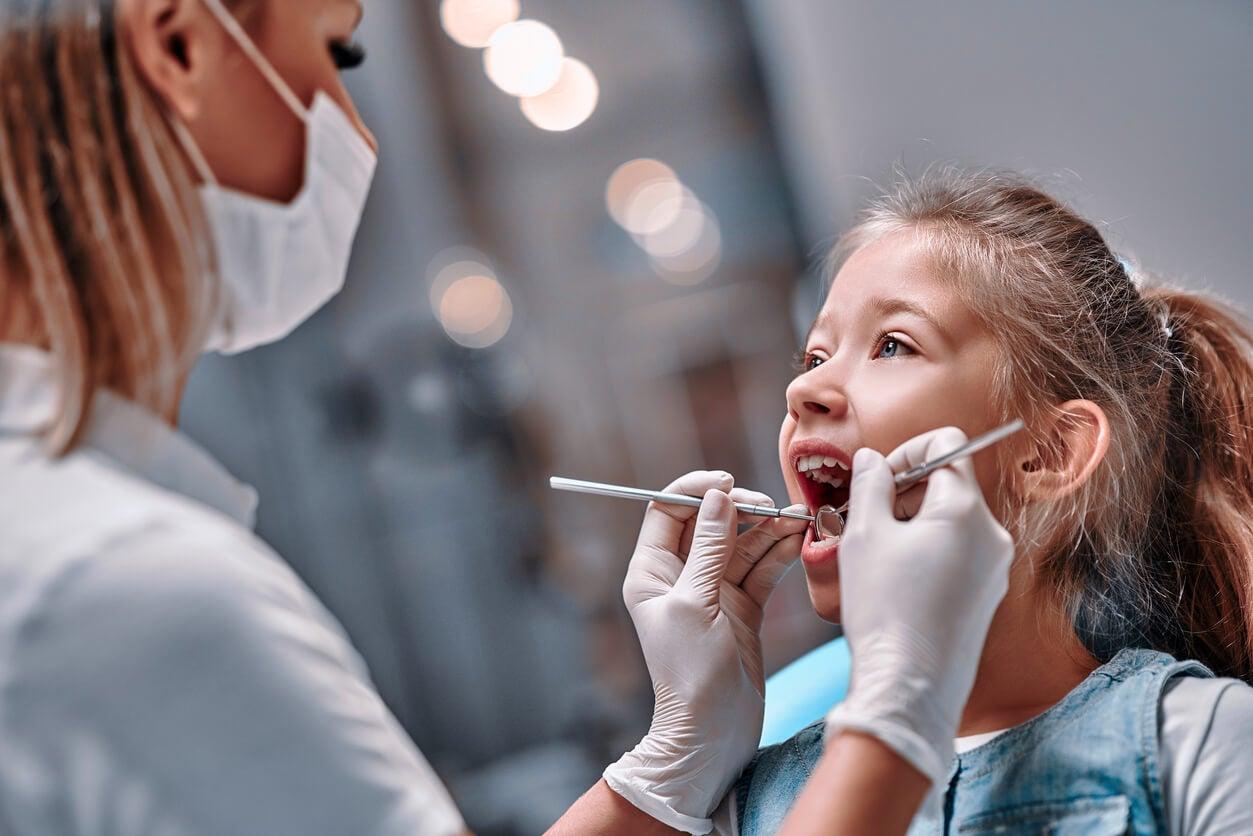 Petite fille chez le dentiste pour découvrir les mauvaises habitudes pour les dents des enfants.