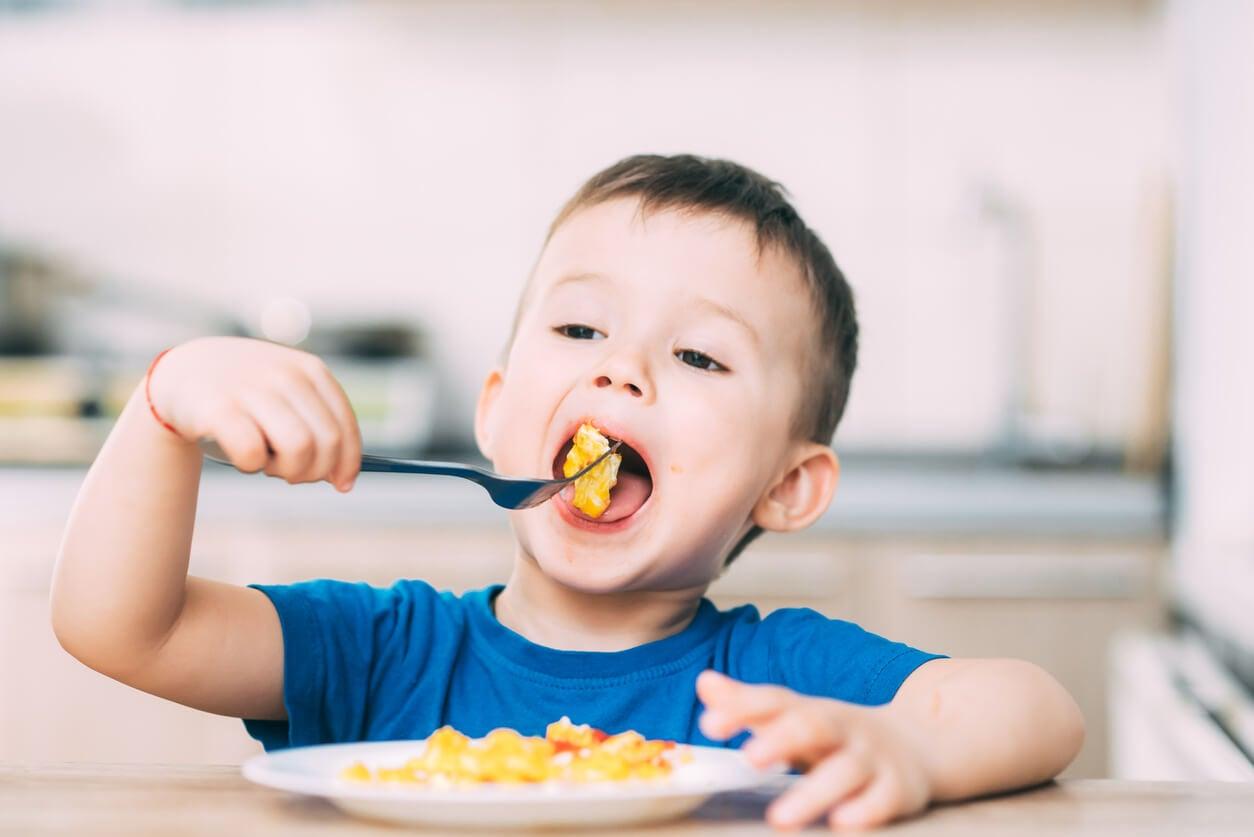 Niño comiéndose toda la comida del plato.