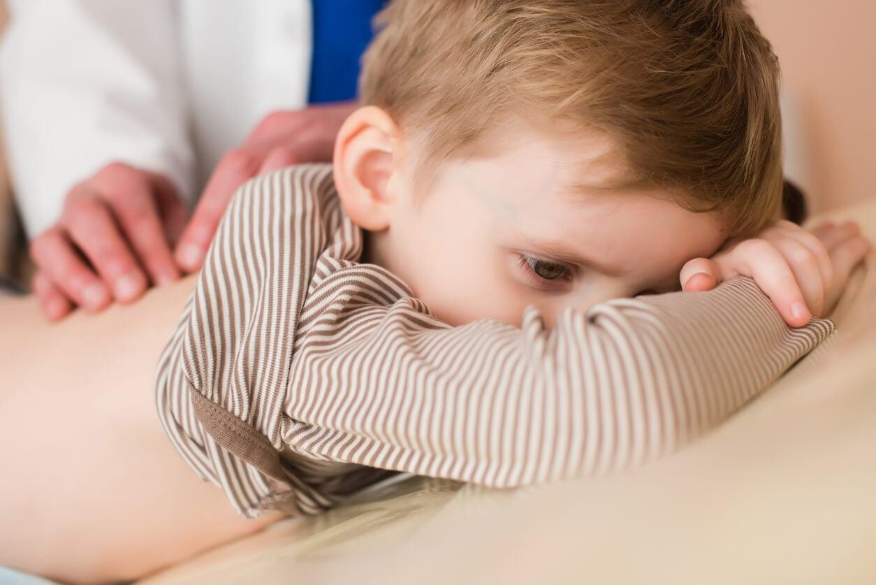 Niño en el médico con dolor de espalda.