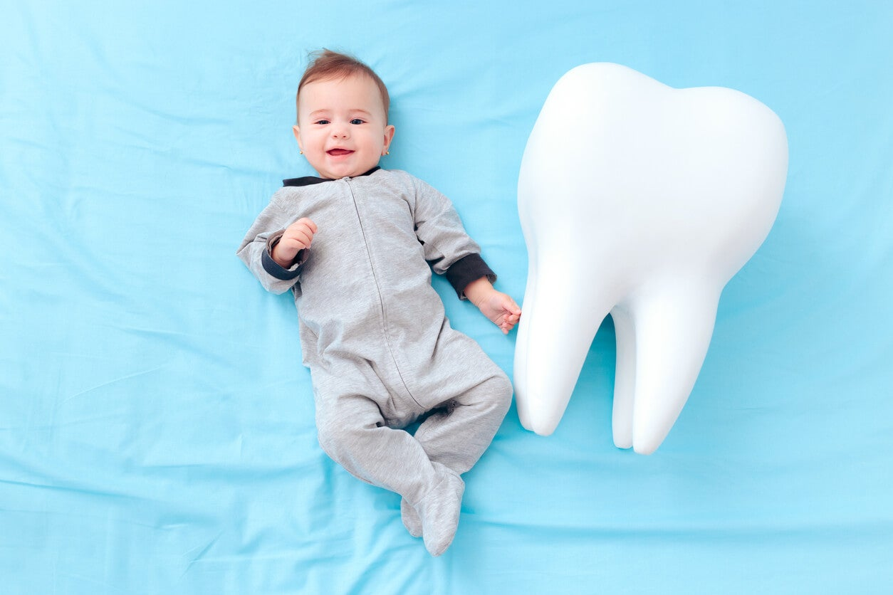 Un bébé à côté d'une dent géante.