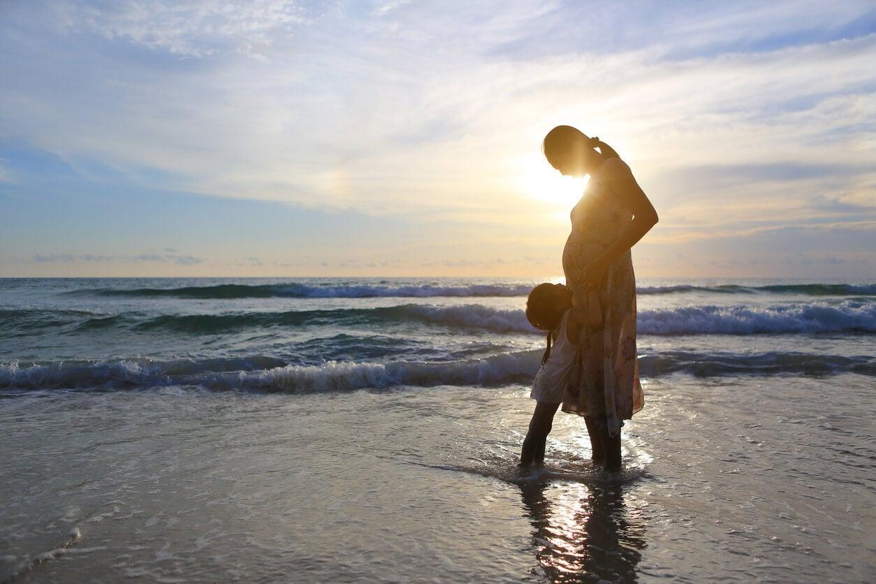 playa atardecer embarazada hija nina mar