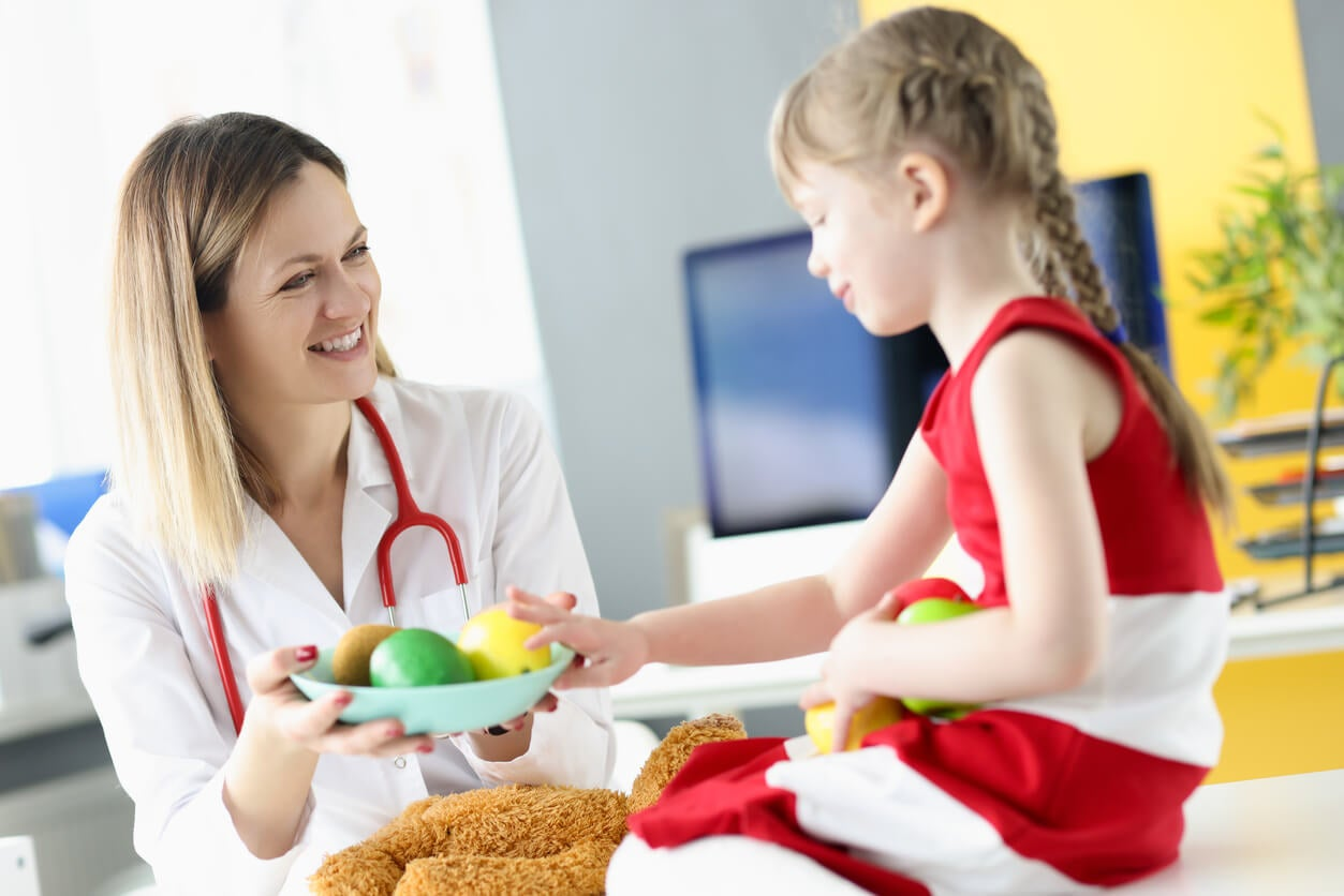Niña en el médico mientras le ofrece comer fruta.