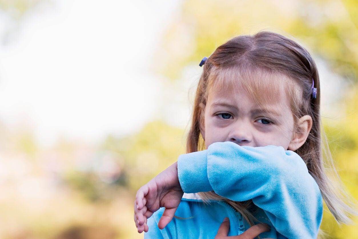 Niña con asma tosiendo.