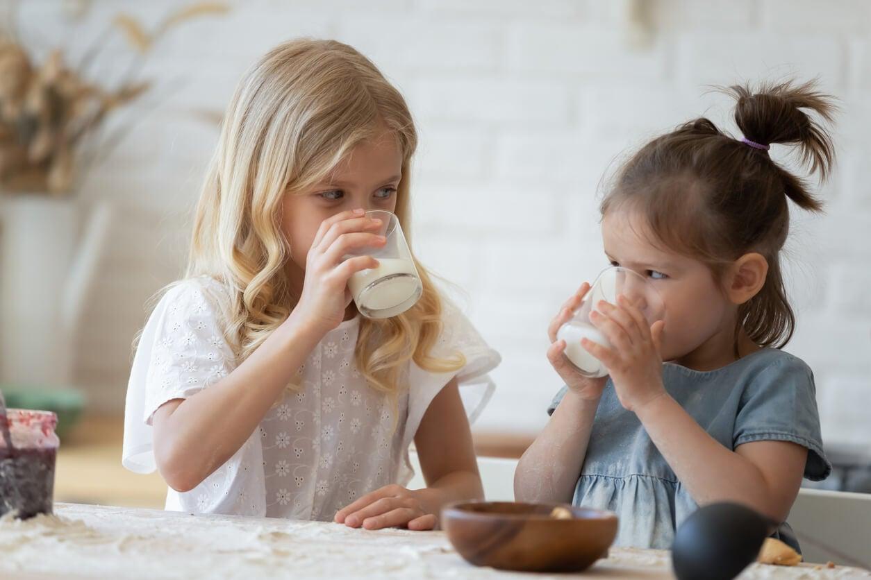 Niñas merendando un vaso de leche según la cantidad adecuada para su edad.