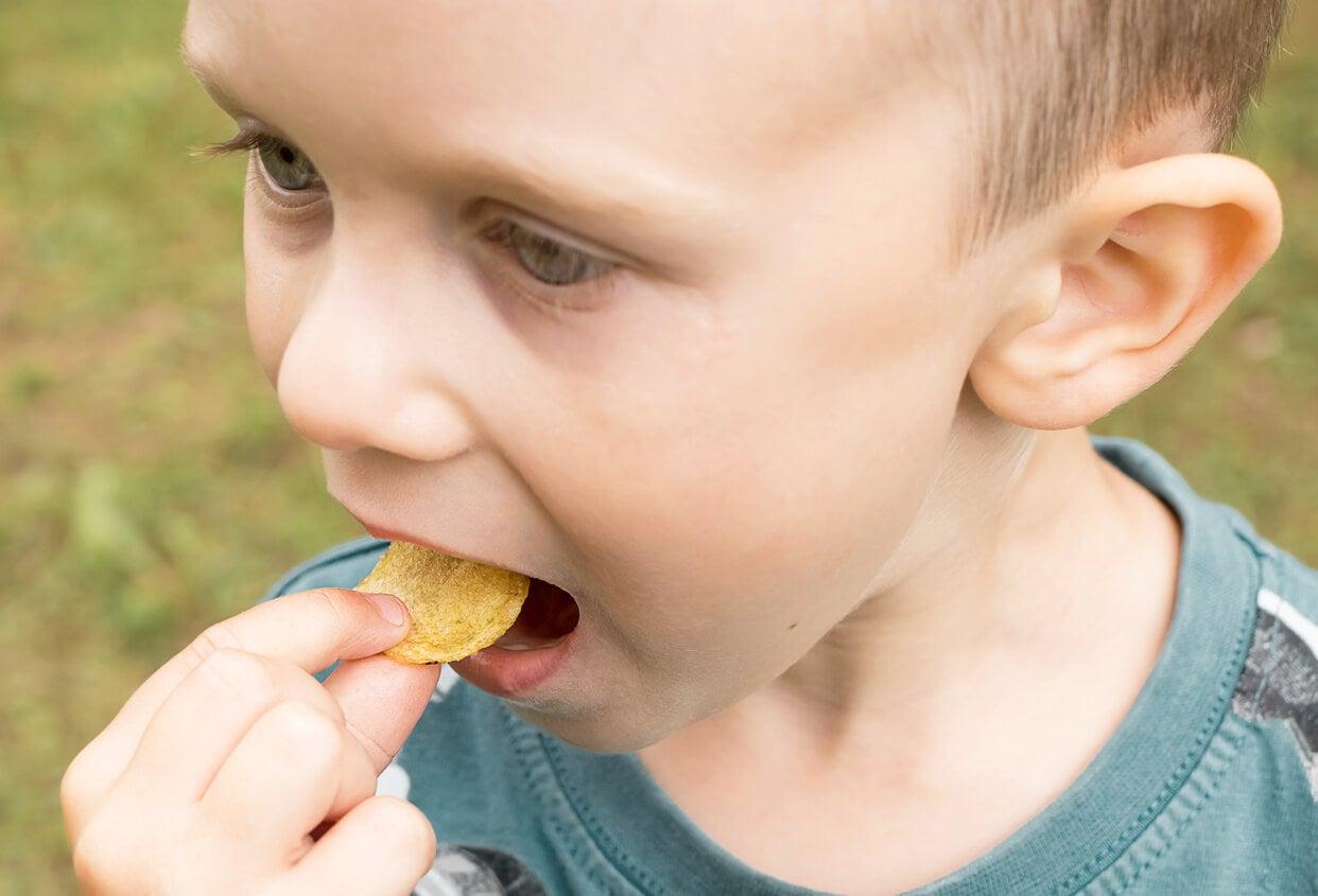 Enfant mangeant des chips avec trop de sel.