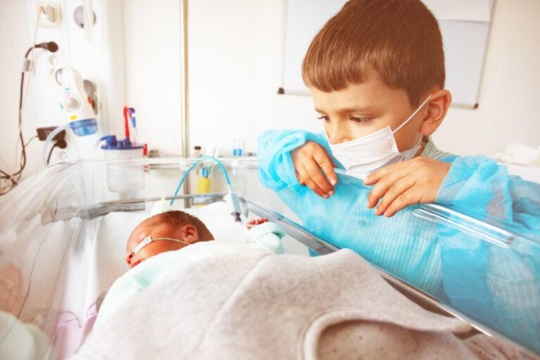 Un enfant masqué qui regarde un bébé prématuré dans sa couveuse.