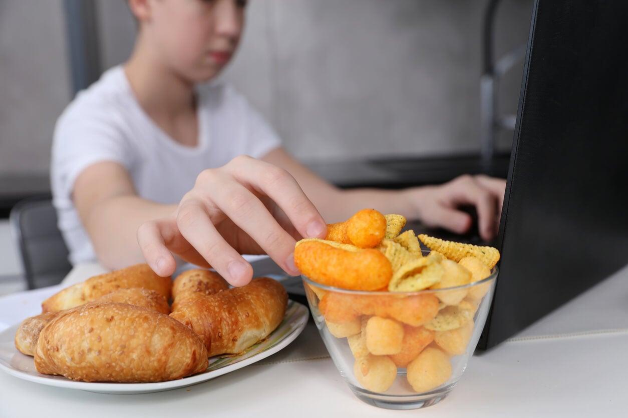 Niño comiendo alimentos ultraprocesados mientras juega al ordenador.