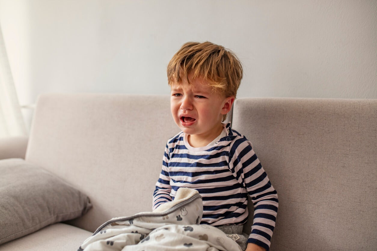 Un enfant qui pleure sur le canapé.
