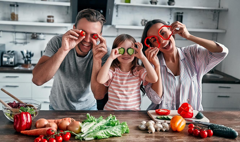 Deux parents avec leur fille qui font la cuisine.