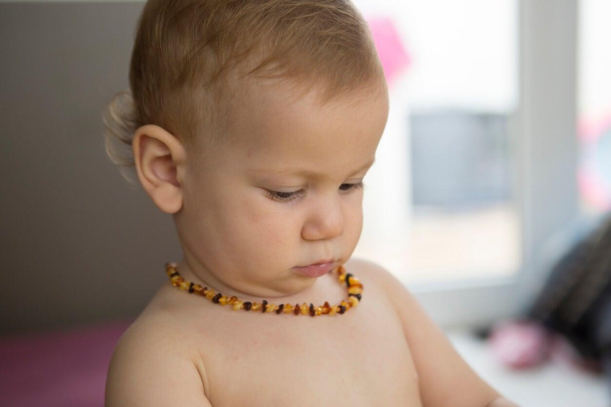 Un bébé avec un collier d'ambre autour du cou.