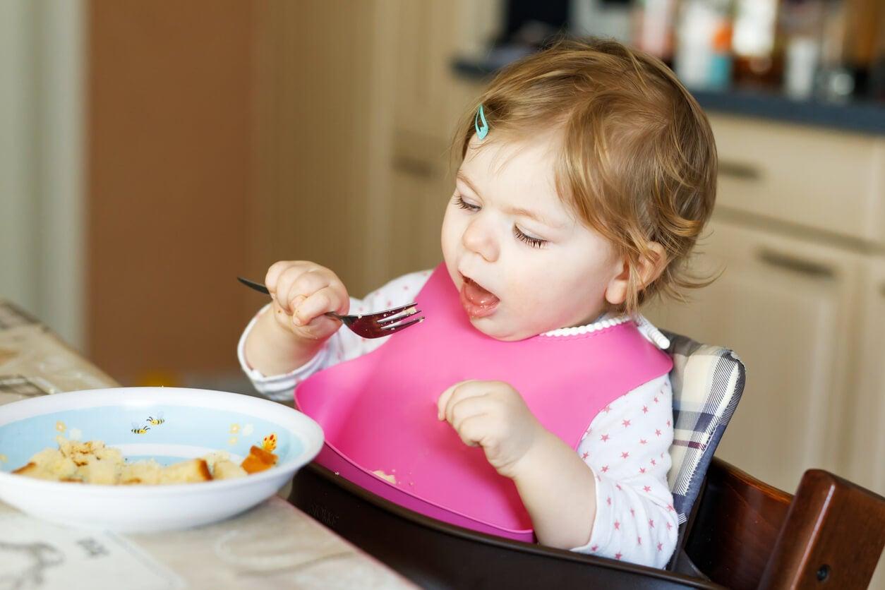 bebe nena nina comiendo sentada silla babero blw tenedor bliss comida alimento plato trozos aprendizaje