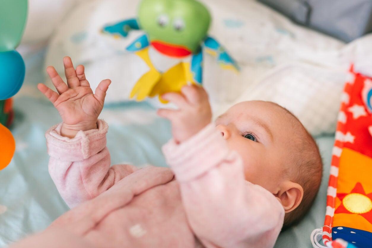 bébé couché couché sur le dos jouet suspendu mobile berceau saisit la main prendre éveillé