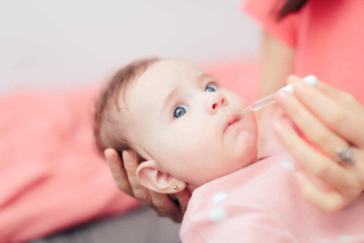 bebe toma medicina jarabe gotas gotero via oral madre mano regazo
