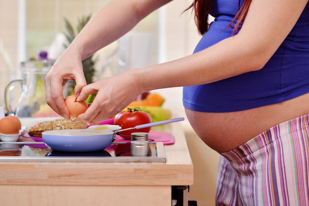 Une femme enceinte qui cuisine.