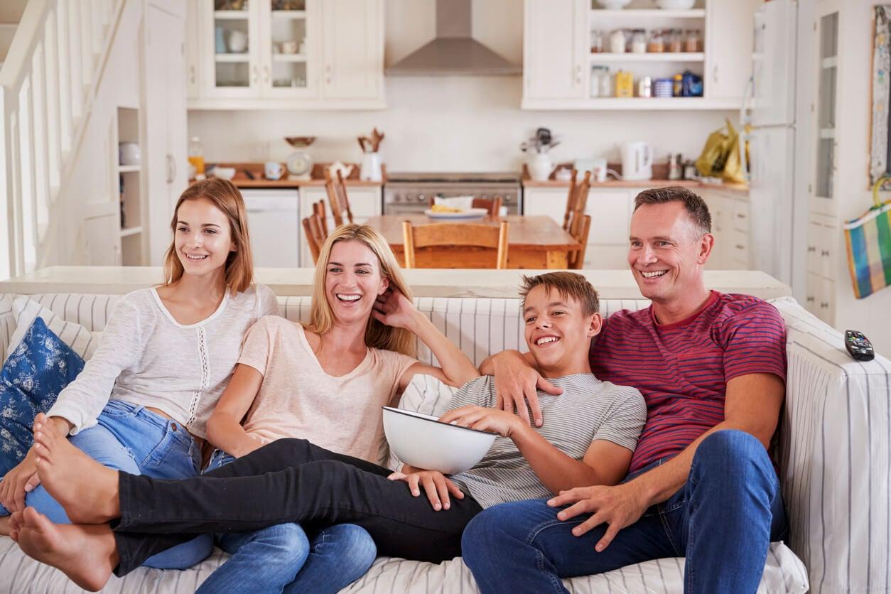 maman mère papa père fils fille adolescente regarder film film canapé salon bonne journée pop corn pop corn