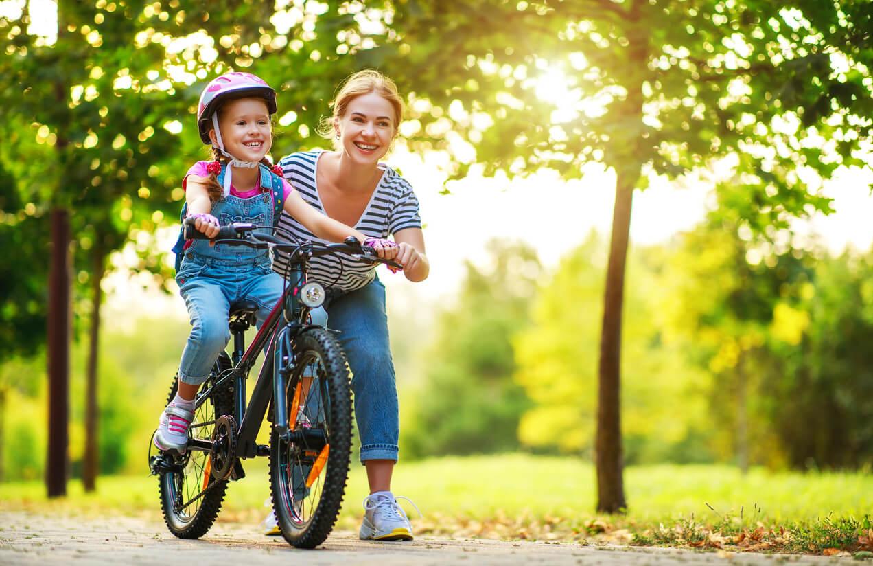 madre ensena nina nena montar pedalear bicicleta parque bosque feliz incentivo casco apoyo enseñanza aprendizaje crianza
