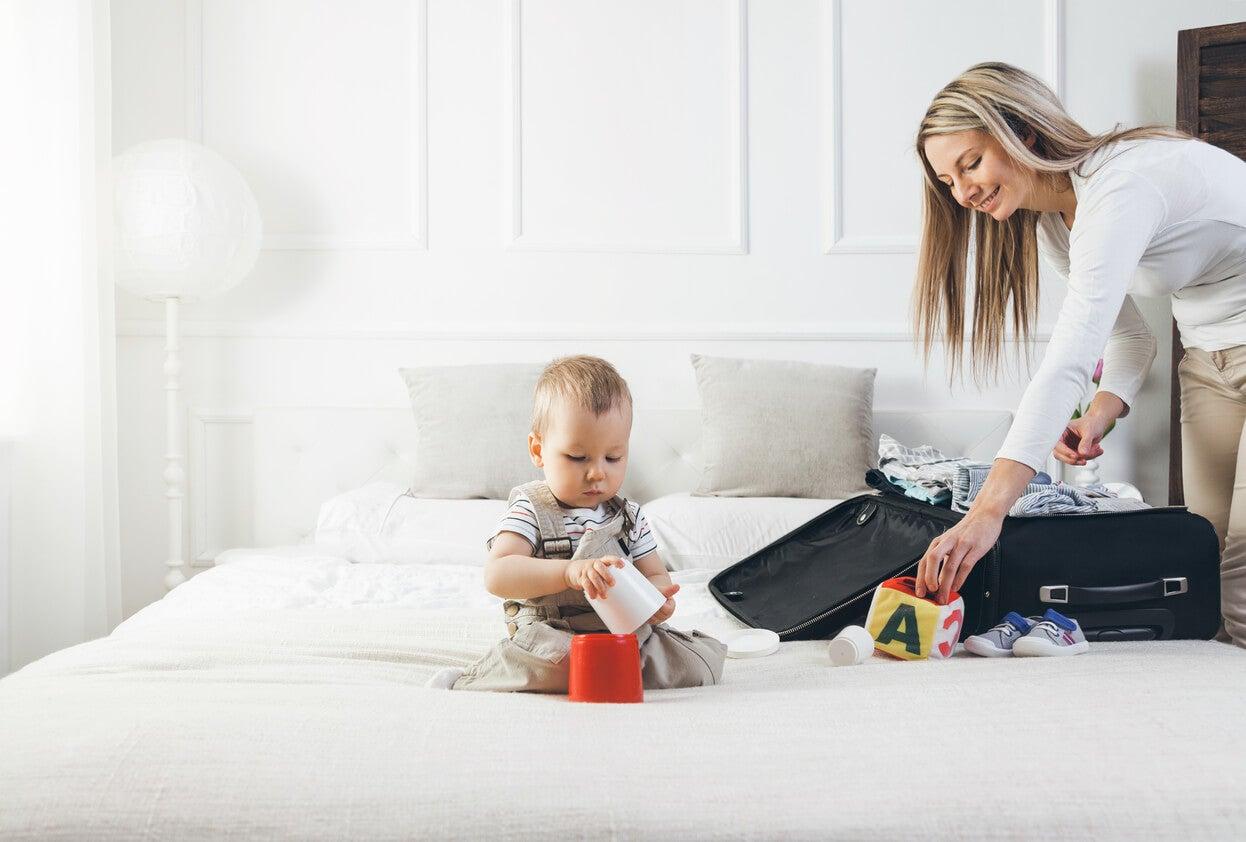vacanza baby mom madre prepara la valigia bambino gioca giocattolo elementi di abbigliamento igiene