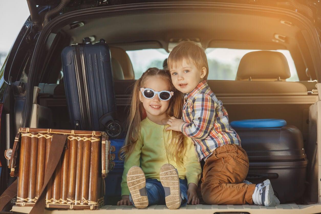 garçon fille frères et sœurs assis coffre voiture valises voyage vacances heureux automne été