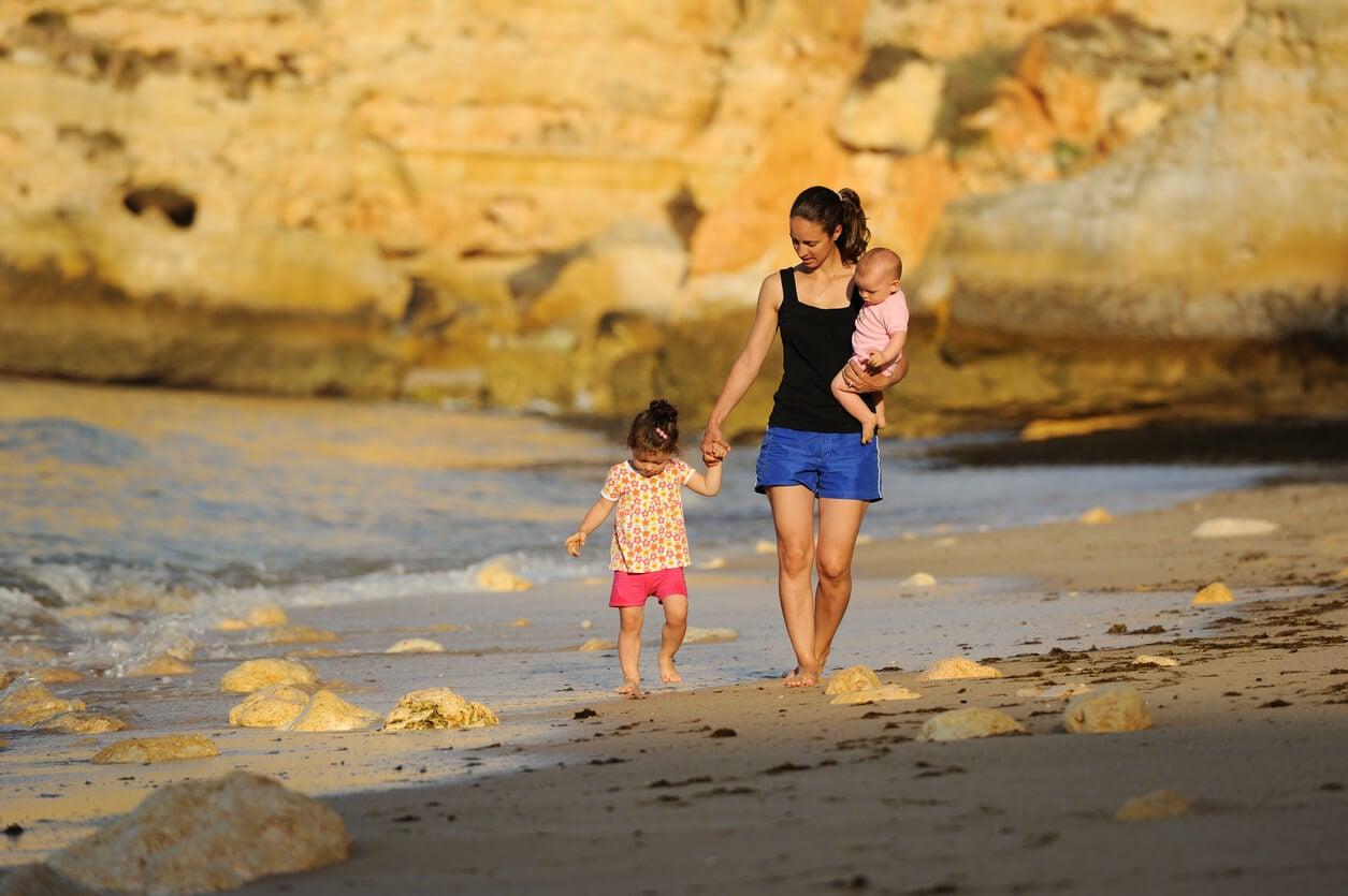 mamma madre cammina spiaggia tramonto figlio bambino estate protezione solare prevenzione lesioni mano upa