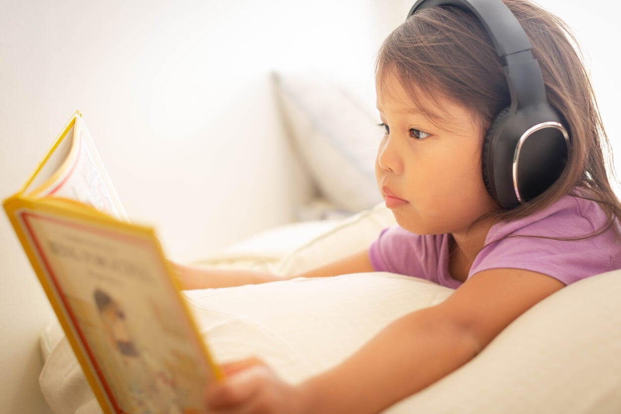 Une jeune fille qui écoute un livre audio.