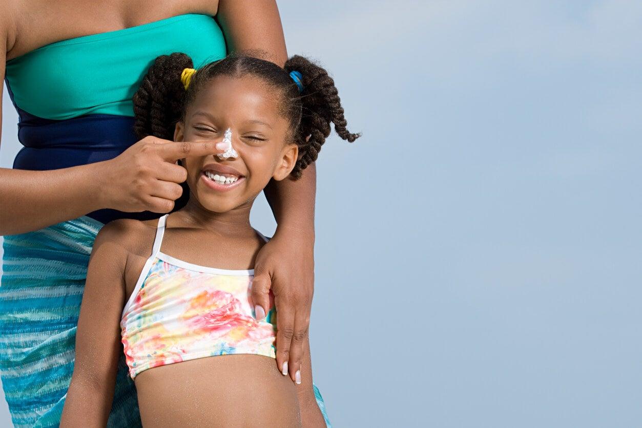 ragazza bambino nero scuro colore della pelle crema solare etnia africana cura della pelle prevenzione lesioni estate costume da bagno
