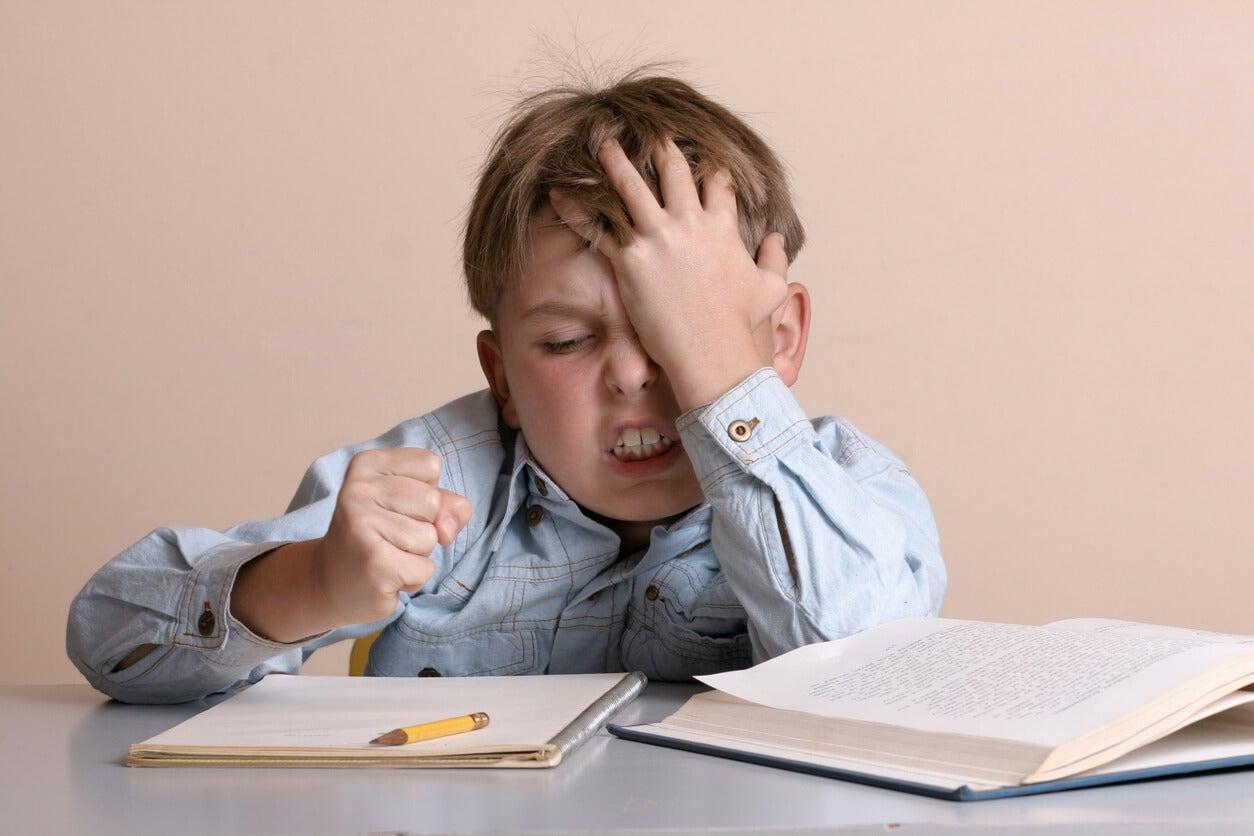 criança zangada frustrada estudo dever de casa livro de dever de casa caderno mesa lápis raiva soco punho bruxismo atm