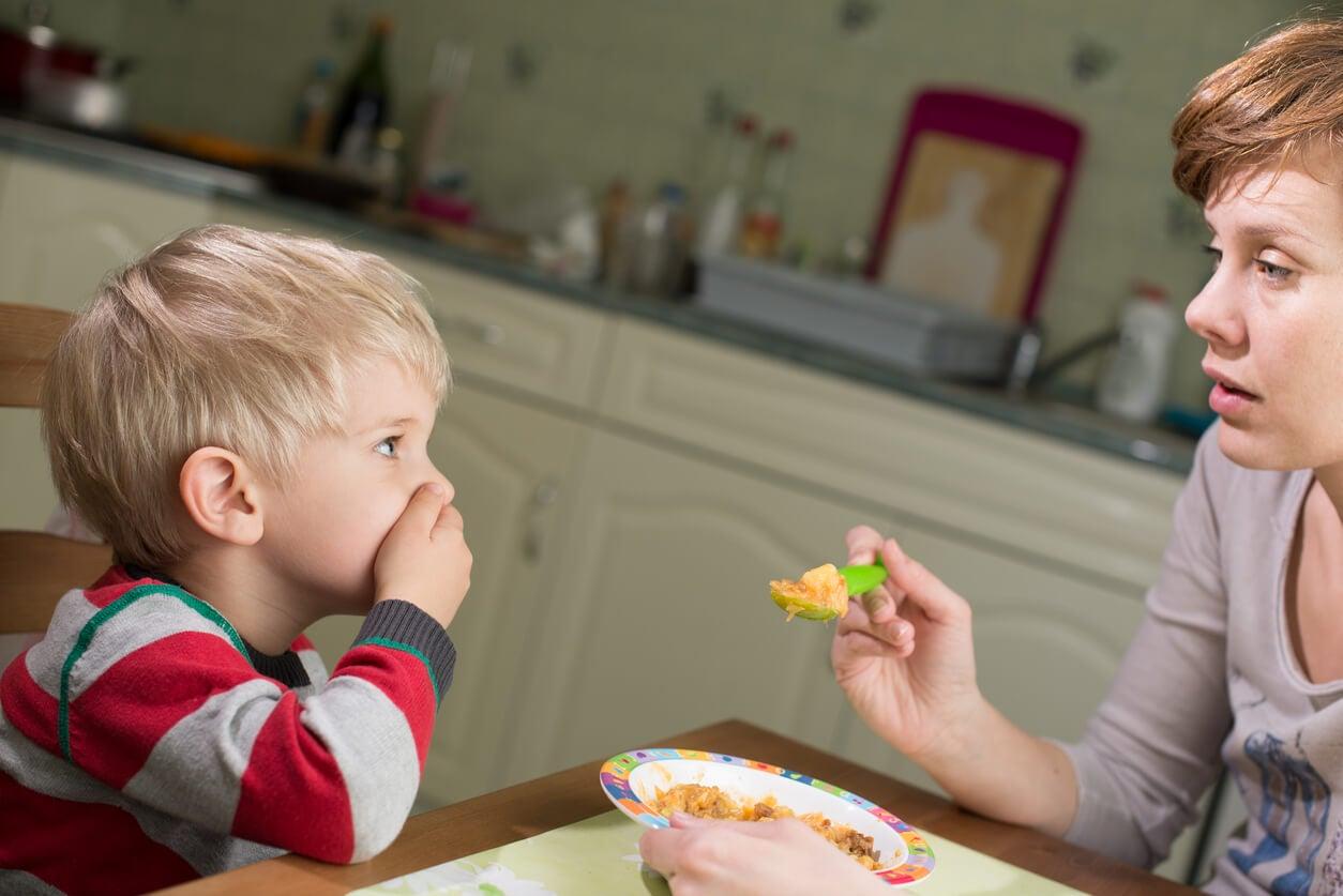 nino nene no quiere comer tapa boca mano mama madre cuchara plato comida rehusa inapetencia fisiologica