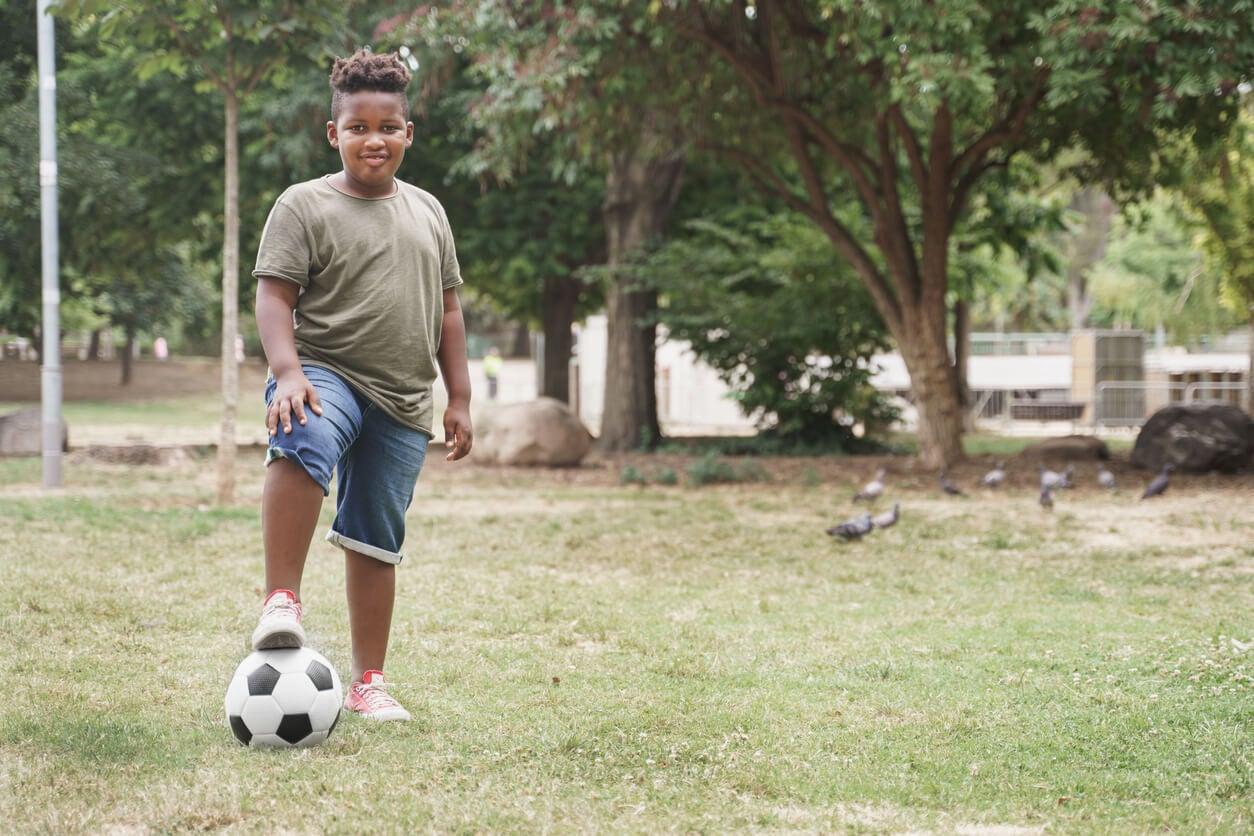 bambino obeso sovrappeso infantile campo da calcio palla attività fisica sport
