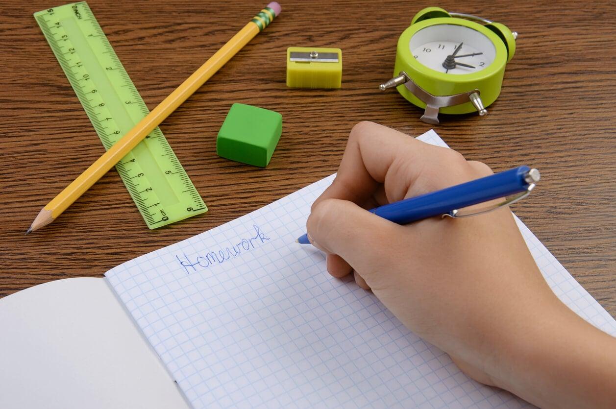 La main d'un enfant qui fait ses devoirs avec un cahier, une règle et des crayons.