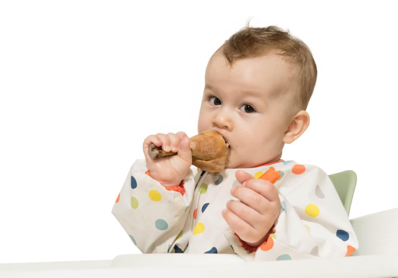 Un enfant qui mange du poulet.